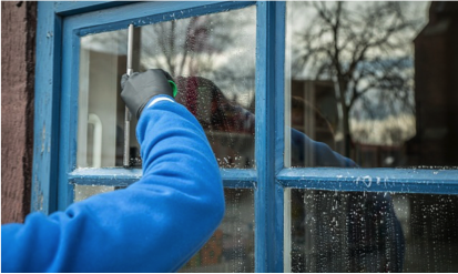 window cleaner washing a window with blue frames